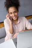 Vänlig ung kvinna som stannar till mobiltelefonen Royaltyfri Bild