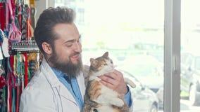 Vänlig veterinär som ler till kameran som rymmer den gulliga vresiga katten stock video