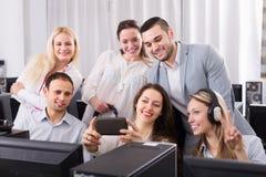 Vänliga coworkers som tar det ömsesidiga fotoet Arkivfoto