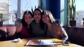 Vänliga förhållanden, flickaomfamning och skratta i ljus matsal stock video