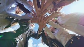 Vänliga kandidater av den höga skolan sätter deras händer på de och öppnar dem mot den blåa himlen Soligt dagsljus lager videofilmer