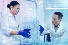 Vänliga kollegor som ler, medan se DNAmodellen Fotografering för Bildbyråer