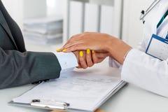 Vänliga kvinnliga doktors händer som rymmer manlig patients hand arkivfoto