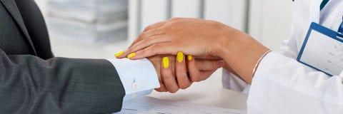 Vänliga kvinnliga doktors händer som rymmer manlig patients hand arkivbilder