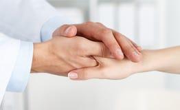 Vänliga manlig doktors händer som rymmer kvinnliga patients hand royaltyfri foto