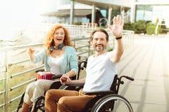Vänliga par i rullstolar som välkomnar en främling fotografering för bildbyråer