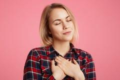 Vänliga snälla -hjärtad kvinnliga stängda uppehälleögon, händer på bröstkorg, uttrycker hennes tacksamhet till någon, poserar mot arkivbilder