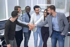 Vänligt affärslag som tillsammans sätter deras händer fotografering för bildbyråer
