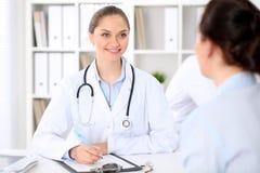 Vänligt le doktors- och patientsammanträde på tabellen Mycket goda nyheter och på hög nivå begrepp för medicinsk service arkivbilder