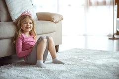 Vänligt liten flickasammanträde på den near soffan för golv arkivbilder