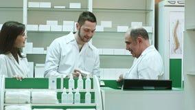 Vänligt medicinskt lag i labblag som diskuterar nya preventivpillerar i apotek stock video