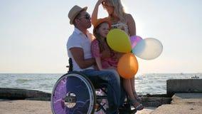 Vännen inaktiverade med familjen, handikapp föräldrar med öppen luft för barn, lyckligt dottersammanträde på farsa med ballonger  stock video