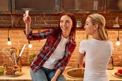 Vänner är solskenet av liv Unga kvinnliga vänner i modernt kök som tillsammans förbereder vegetariskt mål cozy royaltyfri foto