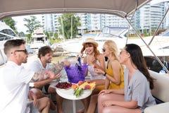 Vänner äter frukter på yachten royaltyfri foto