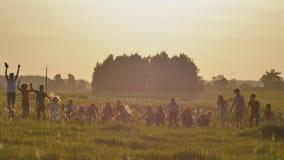 Vänner av skolbarn studsar på solnedgången i solen stock video