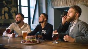 Vänner dricker öl och att äta köttplattan, den hållande ögonen på fotbollsmatchen och att hurra för deras favorit- lag i ljuset stock video