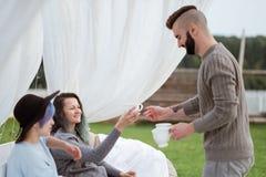 Vänner dricker te och har en bra tid på terrassen av ett landshus fotografering för bildbyråer