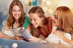 Vänner eller tonåriga flickor som hemma läser tidskriften arkivfoton