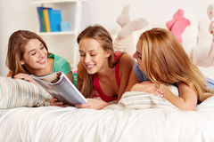 Vänner eller tonåriga flickor som hemma läser tidskriften royaltyfria bilder