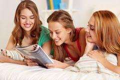 Vänner eller tonåriga flickor som hemma läser tidskriften Arkivfoto