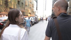 Vänner en man och en kvinna som promenerar en upptagen gata i centret och talar som ler Sikten fr?n baksidan stock video