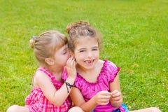 Vänner för barnflickasyster som viskar örat Royaltyfri Fotografi