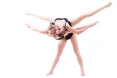 2 vänner för flicka för böjliga idrotts- kvinnor för showgirls nätta lyftte sig på baksidan som gör splittring i luften Fotografering för Bildbyråer
