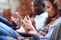 Vänner för Hipsters för Closeupgrupp som vuxna sitter den Sofa Using Hands Modern Smartphone minnestavlan Kamratskap för affärsst Royaltyfri Bild