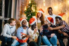 Vänner för julparti på att ha drinken och gyckel royaltyfria bilder