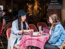 Vänner för unga kvinnor har eftermiddagmellanmålet på det Montmartre kafét, medeltal Arkivfoto