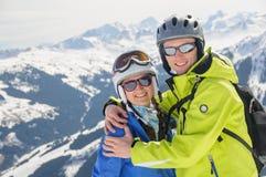 Vänner för vintersport i omfamning på berg Arkivbilder