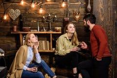 Vänner familj spenderar den angenäma aftonen, inre bakgrund Familjen tycker om konversation i skogsvaktarehus Flickor och royaltyfri foto