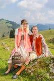 Vänner flåsar i trendig traditionell bayersk Dirndl och läder med hatten Arkivbild