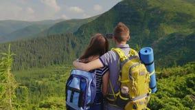 Vänner fotograferar ett härligt berglandskap Tyck om vila tillsammans tillbaka sikt stock video