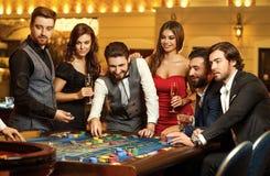 Vänner gör vad som gambiling på rouletttabellen i kasinot royaltyfri fotografi
