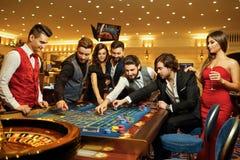 Vänner gör vad som gambiling på rouletttabellen i kasinot fotografering för bildbyråer
