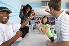 Vänner glädjande på bowlingbanan Royaltyfri Foto