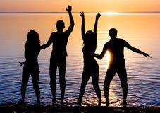 Vänner, grabbar och flickor, studenter dansar på solnedgångbackgrouen Royaltyfria Foton