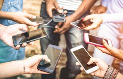 Vänner grupperar att ha missbrukat gyckel som använder tillsammans smartphones royaltyfri fotografi