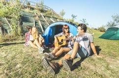 Vänner grupperar att ha roligt utomhus- bifall på picknicklägret arkivfoton