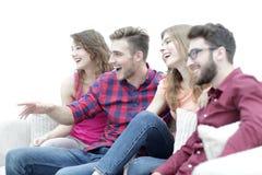 Vänner håller ögonen på ditt favorit- showsammanträde på soffan arkivbild