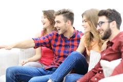 Vänner håller ögonen på ditt favorit- showsammanträde på soffan royaltyfria bilder