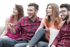 Vänner håller ögonen på ditt favorit- showsammanträde på soffan arkivbilder