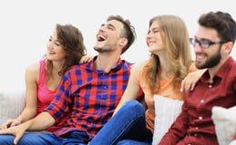 Vänner håller ögonen på ditt favorit- showsammanträde på soffan royaltyfria foton