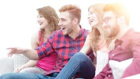 Vänner håller ögonen på ditt favorit- showsammanträde på soffan arkivfoton