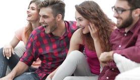 Vänner håller ögonen på ditt favorit- showsammanträde på soffan royaltyfri foto
