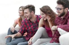 Vänner håller ögonen på ditt favorit- showsammanträde på soffan fotografering för bildbyråer