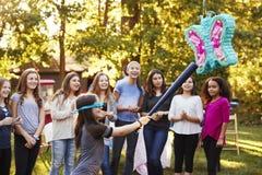 Vänner håller ögonen på en ung flicka att slå en ata för piï¿ ½ på hennes födelsedag royaltyfria bilder