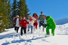Vänner har gyckel på vintern på ny snö Royaltyfri Foto