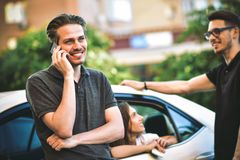 Vänner har konversation på gataanseende nära bilen arkivbild